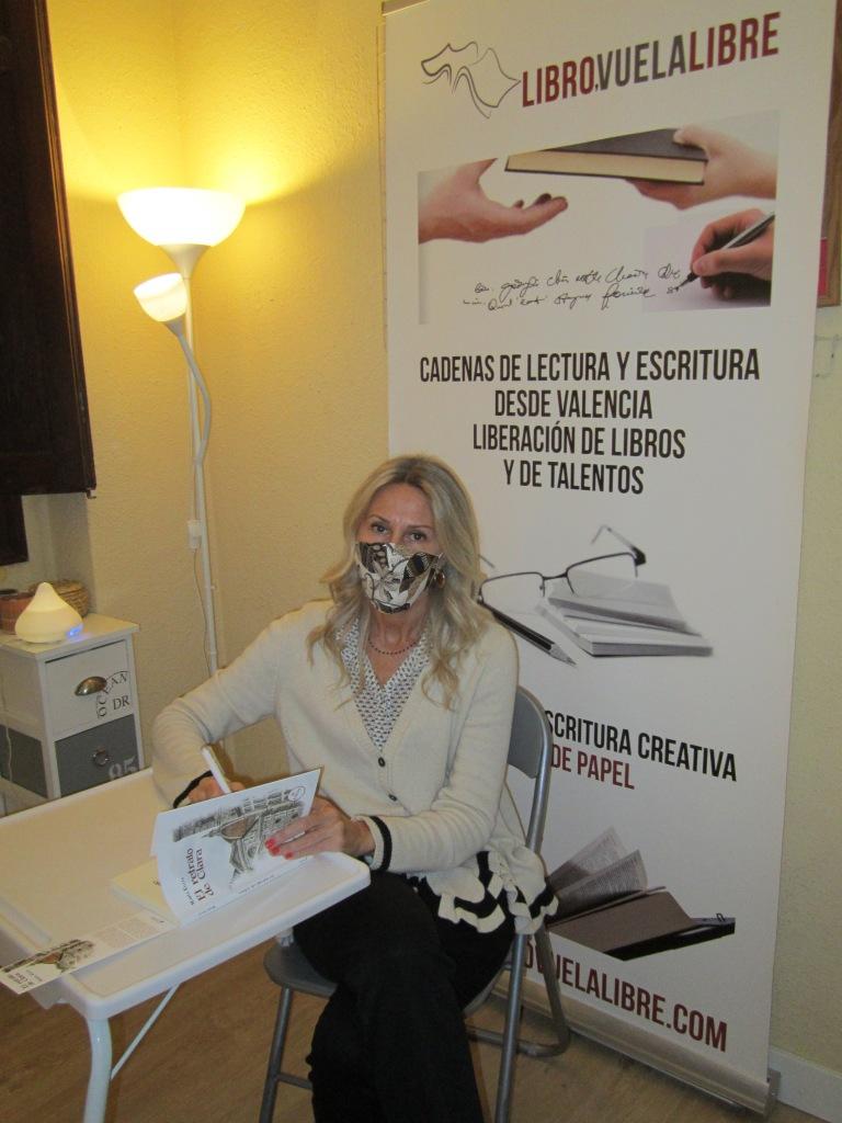 María Eguía firmando para la biblioteca de talentos de los talleres literarios de Libro vuela libre en Valencia un ejemplar de su novela El retrato de Clara